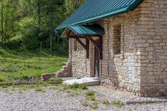 与绿色三角形屋顶的石农舍在绿色庭院背景  图库摄影
