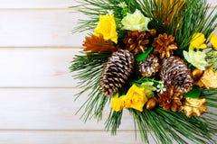 与黄色丝绸玫瑰和金黄杉木锥体的圣诞节背景 图库摄影