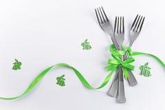 与绿色兔宝宝的三把孩子的党的叉子和装饰 图库摄影
