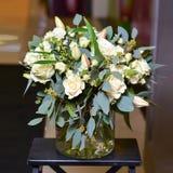 与绿色分支和奶油色玫瑰的花束 库存照片