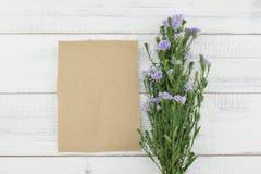 与紫色切削刀的空白的棕色卡片开花花束 免版税图库摄影