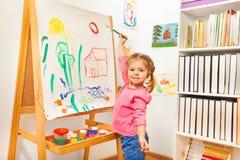 与绿色刷子的女孩绘画在画架 库存照片