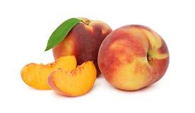与绿色叶子和切片的两个整个桃子(被隔绝) 免版税库存照片