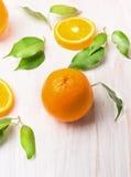 与绿色叶子和切片的未加工的橙色果子 图库摄影