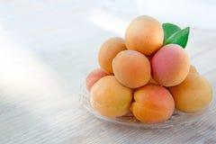 与绿色叶子的新鲜的成熟杏子由在一块玻璃板的一座金字塔组成,照亮由太阳 木背景 库存图片