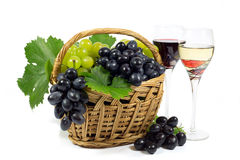 与绿色叶子的新鲜的红色和白葡萄在柳条筐和两酒杯杯充满被隔绝的红色和白葡萄酒 免版税图库摄影