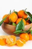 与绿色叶子的新鲜的蜜桔在一个木碗 免版税库存图片