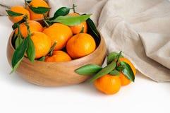 与绿色叶子的新鲜的蜜桔在一个木碗 免版税库存照片