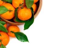 与绿色叶子的新鲜的蜜桔在一个木碗 库存图片