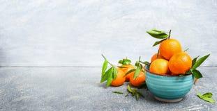 与绿色叶子的新鲜的蜜桔在土气背景,侧视图的蓝色碗 免版税库存图片