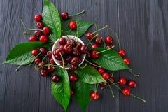 与绿色叶子的甜新鲜的樱桃在蓝色土气木头 免版税库存照片