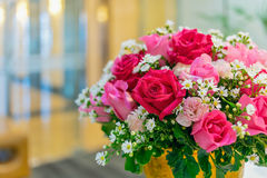 与绿色叶子的红色和桃红色玫瑰在瓶子 免版税库存照片
