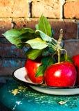 与绿色叶子的红色大苹果在土气葡萄酒背景, c 库存照片