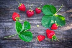 与绿色叶子的草莓在一个织地不很细委员会 免版税库存照片