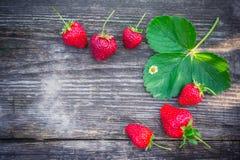 与绿色叶子的草莓在一个织地不很细委员会 免版税图库摄影