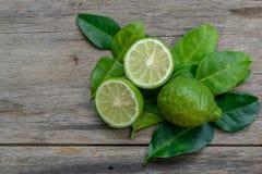 与绿色叶子的香柠檬在木头 免版税库存照片