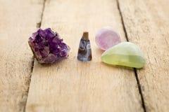 与紫色和淡绿色的水晶的灼烧的香火锥体与 库存照片