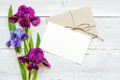 与紫色和蓝色虹膜的空白的白色贺卡开花花束和信封 库存照片
