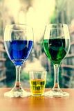 与绿色和蓝色鸡尾酒黄色射击的玻璃 免版税库存照片