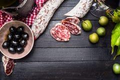 与绿色和黑橄榄开胃小菜和红葡萄酒的切的意大利蒜味咸腊肠在黑木背景,顶视图,文本的地方 免版税图库摄影