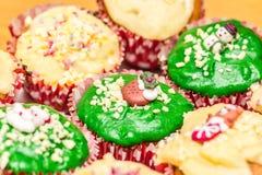 与绿色和黄色结冰的圣诞节杯形蛋糕 免版税库存图片