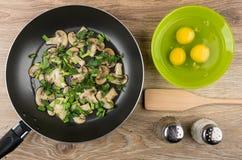 与绿色在煎锅,未加工的鸡蛋的油煎的蘑菇 免版税库存图片