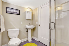 与紫色地板和轻的米黄墙壁的简单的卫生间内部 库存图片