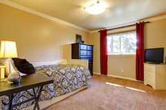 与黄色墙壁和电视的卧室内部。 图库摄影