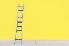 与黄色墙壁的蓝色钢梯子 库存图片