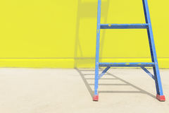 与黄色墙壁的蓝色钢梯子 库存照片