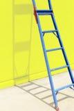 与黄色墙壁的蓝色钢梯子 图库摄影