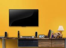 与黄色墙壁的被带领的电视木桌在客厅 库存照片