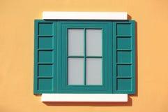与黄色墙壁的绿色窗口 免版税库存图片