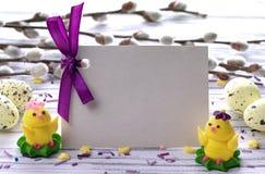 与黄色复活节彩蛋褪色柳的复活节背景分支紫色丝带和一点鸡空间文本的 免版税库存照片