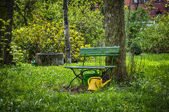 与黄色大口水罐的庭院长凳 免版税库存图片