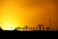 与黄色天空的滑雪电缆车剪影 免版税库存图片