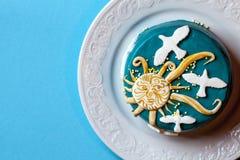 与黄色太阳和白色鸠的小复活节蓝色蛋糕在白色板材 背景看板卡祝贺邀请 图库摄影