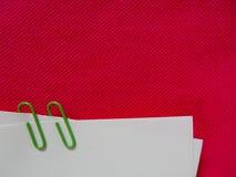 与绿色夹子的纸笔记在桃红色织品 免版税库存图片