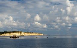 与黄色岩石和云彩形成在金黄日落小时,温暖的晚上光,风景的美好的海视图 免版税库存照片