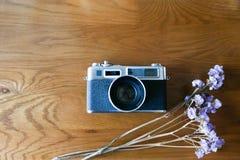 与紫色干燥花的彩色片照相机在与拷贝空间的木桌面看法 库存照片