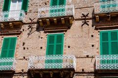 与绿色快门的意大利石房子前面 库存照片