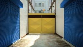 与黄色快门,蓝色辗压门的工厂入口 图库摄影