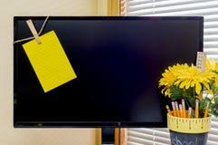 与黄色提示笔记的大规模计算机显示器截去了到左边 免版税库存照片
