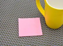与黄色杯子的笔记薄在样式背景 免版税图库摄影