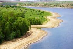 与绿色树的晴朗的河海滩 免版税库存图片