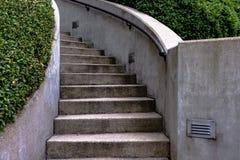 与绿色树篱的弯曲的具体楼梯 库存图片