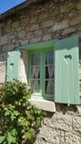 与绿色框架和木快门和花边窗帘的窗口 库存图片