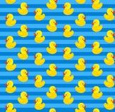 与黄色橡胶鸭子的逗人喜爱的无缝的样式在蓝色背景 库存图片