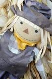 与黄色班丹纳花绸的灰色稻草人 库存照片
