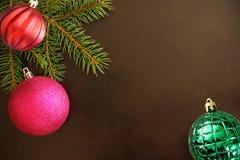 与紫色的圣诞树分支,在黑暗的背景的红色波浪和绿色有肋骨球 免版税库存照片